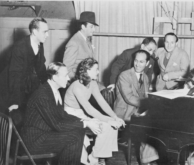 """George Gershwin, sentado al piano, con Ginger Rogers, Fred Astaire y otros, en el plató donde se filmaba """"Shall We Dance?"""" (1937)"""