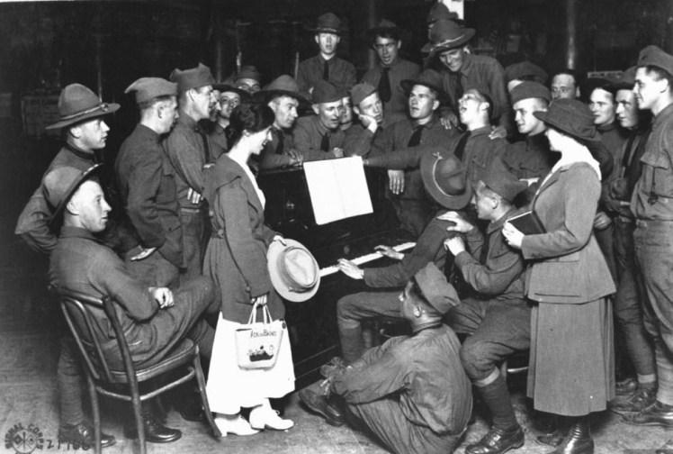 Soldados estadounidenses y muchachas de la Young Men's Christian Association (YMCA) cantando alrededor de un piano en Aix-les-Bains (Francia) en agosto de 1918