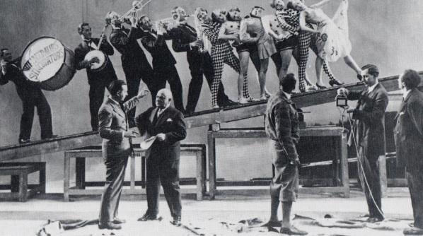 """Rudolf Nelson (en la fila de abajo el segundo por la izquierda) con las 'chicas Nelson' y los Weintraub Syncopators en un fotograma del cortometraje de 1929 """"Und Nelson spielt""""."""
