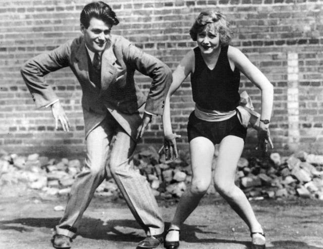 Pareja de jóvenes bailando el charlestón en los años 20.