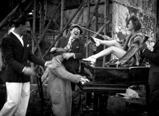 Mischa Spoliansky (al piano) con el tenor Richard Tauber (clavándole el sombrero) en los estudios de la UFA. Ella parece que es Georgia Lind.