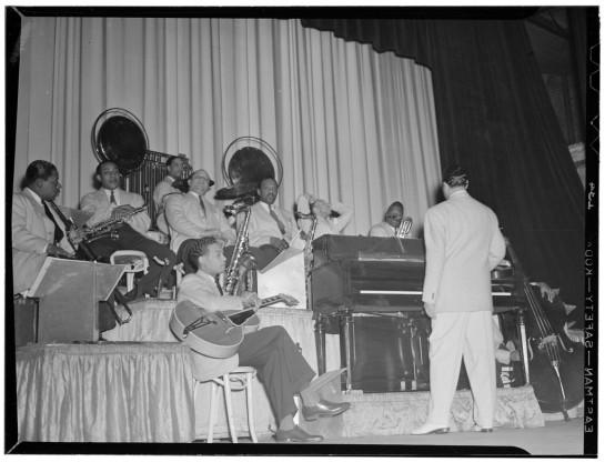 Ben Webster (el sexto en la imagen de izquierda a derecha, junto al piano) con la Orquesta de Duke Ellington. Fotografía de 1940-1942.