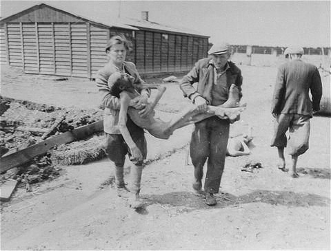 Civiles de Dachau transportando cadáveres a los carromatos.