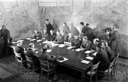 El Jefe del Estado Mayor del Alto Mando de las fuerzas armadas alemanas, el general Alfred Jodl, firma, rodeado de otros jerarcas nazis, el acta de rendición incondicional para todas las fuerzas alemanas ante los Aliados. Reims, 7 de mayo de 1945.