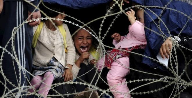 Una niña refugiada llora tras la alambrada que impide cruzar la frontera entre Grecia y Macedonia. / REUTERS