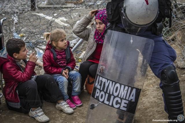 Niños refugiados custodiados por un policía griego en la frontera con Macedonia